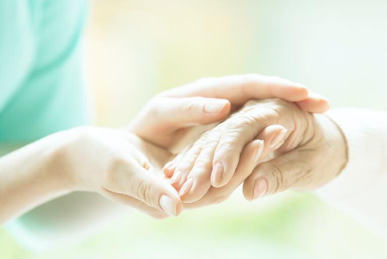 患者様の手を支えるスタッフ